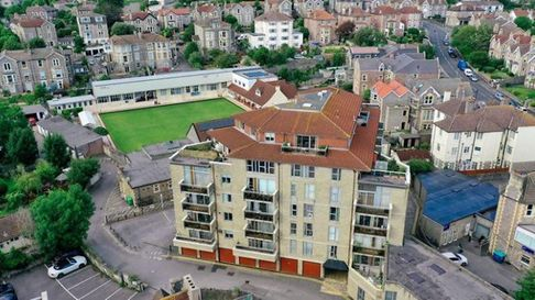 aerial shot of six-floor apartment block in Boulevard, Weston with bowling green behind and town centre buildings surrounding