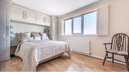 white bedroom with fitted furniture around a king-size bed, wooden floor and large triple window with shutters and radiator