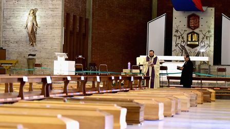 Priest Don Mario blesses the coffins of COVID-19 victims at the church of San Giuseppe before they a