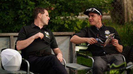Promoter Chris Louis and team manager Ritchie Hawkins talk tactics in the sun ahead of the meeting.