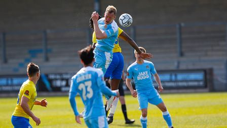 Josh Umerah of Torquay United challenges for the aerial ball with Mark Ellis of Notts County during