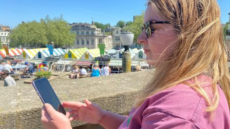 Reporter Louisa Baldwin at Norwich Market solving a clue on the Clued Up! Escape Rooms outdoor game.