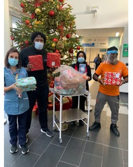 Mr Charles, on the right, delivers gifts to sick children at Newham University Hospital.