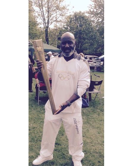 Mr Charles holds the Olympic torch