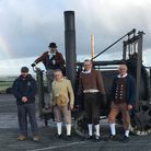 4 men in period dress stand in front of a replica of a steam locomotive from 1801