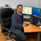 Dr NajibSeedat, a partner at Ilford Medical Centre, sitting at a desk in front of a computer