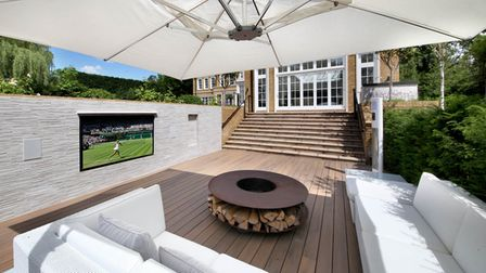 Outdoor lounge area attached to external kitchen in luxury home.