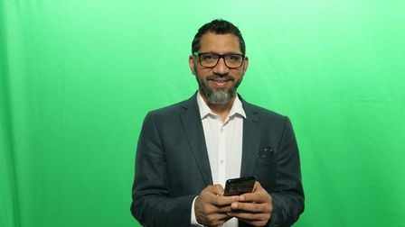 Idris Patel wearing a suit, holding a phone, in front of a green background