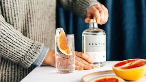 A bottle of Pentire next to a glass of the drink with tonic, topped with a slice of grapefruit and ice