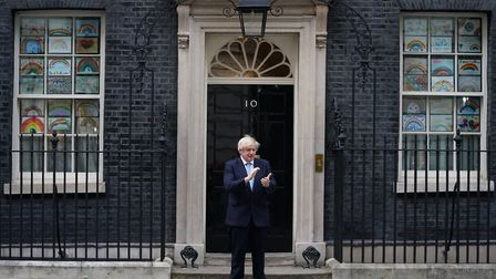 Prime Minister Boris Johnson stands in Downing Street to join in the applause to salute local heroes