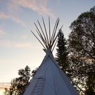 A teepee is backed by trees and the open sky as dusk falls