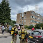 Firefighters and residents outside a block of maisonettes inQueenswood Gardens, Wanstead