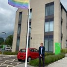Councillor Joe Whibley by the Pride flag at East Devon District Council's Blackdown House offices in Honiton