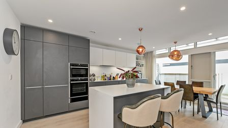 The kitchen area is fitted with modern units, integrated appliances, and a breakfast island.