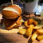 Burger on a wooden board with hand cut chips