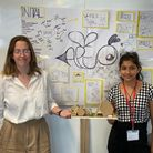 Antonia Arbova and Dhara Zaveri presenting their design for the People's Pavilion competition, stood in front of a whiteboard