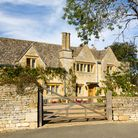 A country house behind a stone wall with a brown gate
