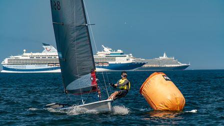 Action from the weekend's sailing - a sailor racing at sea with a cruise ship behind him