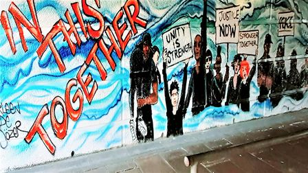 The mural displays the message 'in this together', accompanied by figures holding signs in protest