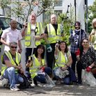A group of litter pickers wearing high viz jackets on a residential street