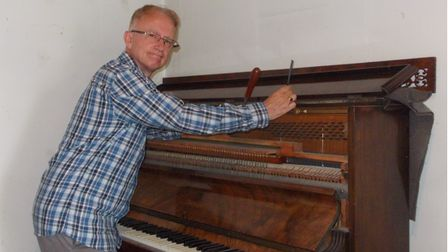 Showing patience with a family heirloom... piano tuner Steven Harris.