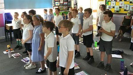 Children stand up in a classroom and sing