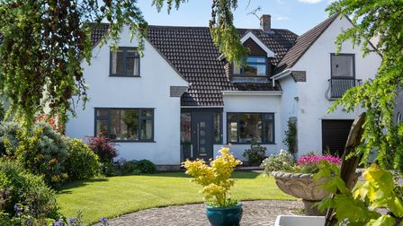 exterior of white house in wick st lawrence with eaves and pretty landscaped garden with path, framed with trees and pots
