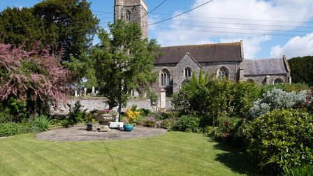 immaculate lawned garden framed by trees and shrubs, overlooking wick st lawrence church