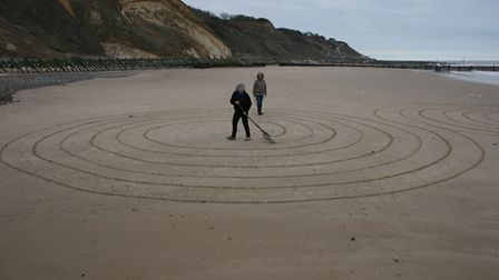 Cynthia Byers and Mary Green drawing out a labyrinth on Overstrand beach.