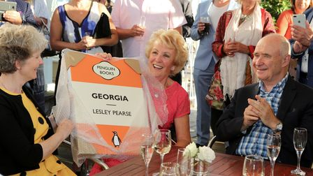 she's holding a canvas of a Penguin Classics cover of her first book, Georgia, which was gifted to her by her publisher