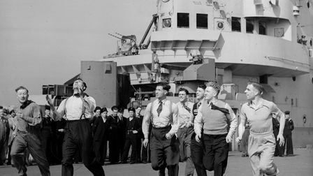 The British Lions rugby league team toss a ball around on the deck of the aircraft carrier HMS Indomitable