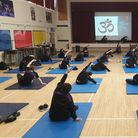 Pupils in a school hall try out yoga.
