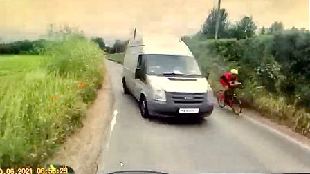 Motorcyclist's POV: A very narrow road. A van takes up most of the space. To the right, a cyclist.