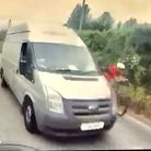 Motorcyclist's POV: the rider is pulled into the verge. The van overtakes the cyclist with little berth either side