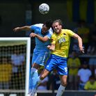 Joe Lewis of Torquay United challenges for the aerial ball with Kyle Wootton of Notts County during