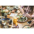 Hands view of young people eating brunch and drinking smoothies bowl with ecological straws in plast
