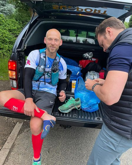 John and his support team stopping to sort out his blisters during his 24-hour marathon!