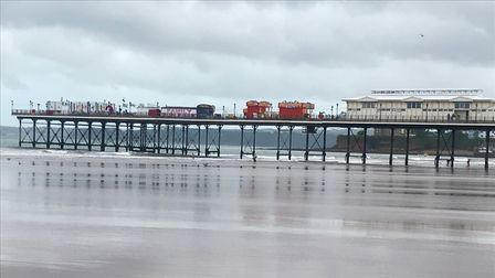 Paignton Pier with the tide going out showing a lovely sandy beach.