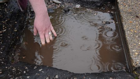 Francesca Bolingbroke shows how deep the pothole on the footpath at the entrance to the Beechcroft S