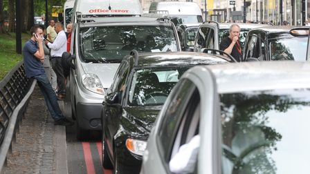Drivers stand alongside stationary cars in a traffic jam in central London