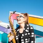 A woman wearing glasses smile. She holds a saxophone