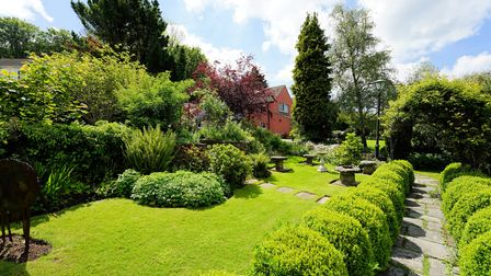 back of house with extensive landscaped gardens in front with shrubs and path with box bushes flanking