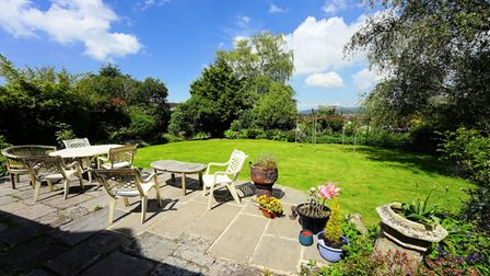 patio with furniture and pots, lawn behind with trees and shrubs surrounding it in farmhouse in Backwell