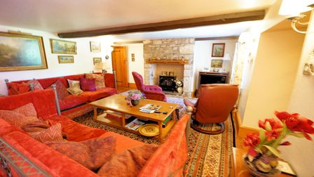 living room with terracotta sofas, wooden coffee table, patterned rug, stone fireplace at the back and ceiling beams