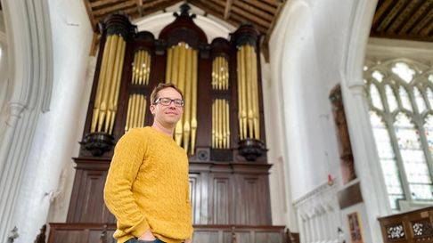 A man wearing yellow stands in front of a large organ in a church