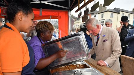 The Prince of Wales inspects a pot of curried goat at the Fancy That Caribbean Catering Company as h