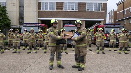 Neil Cash receives a farewell plaque from colleagues at Wembley Fire Station