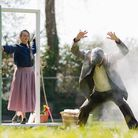 A woman stands in a door frame watching a man dance surrounded by smoke as part of an outdoor play