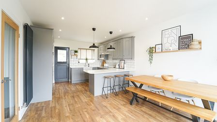 kitchen-dining room with wooden floor, grey units with breakfast bar with downlighters, wooden workbench