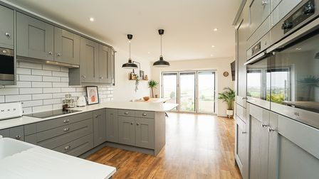 kitchen with modern grey units, white brick-effect tiling and built-in double oven and dining room with bi-folding doors